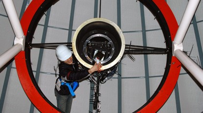 A technician adjusts a telescope lens